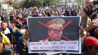A protester holds a placard with a defaced image of Myanmar military Commander-in-Chief Senior General Min Aung Hlaing.