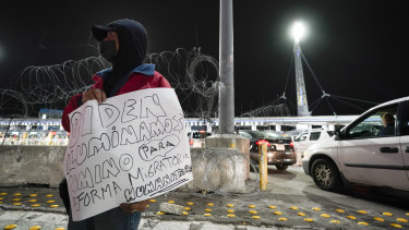 A man holds a sign during a vigil in support of migrants as he stands at the entrance to the San Ysidro port of entry along the US-Mexico border in Tijuana.