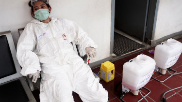 A member of the Indonesian Red Cross Society takes a break after spraying disinfectant at the Kemayoran train station in Jakarta.