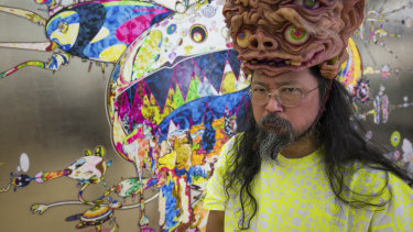 Takashi Murakami, wearing a headpiece from  Amazing Studio JUR, in front of his artwork Tan Tan Bo Black Hole (2019).