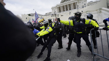 Trump supporters try to break through a police barrier outside the US Capitol in Washington DC.