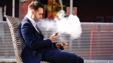 A man vapes on Bourke Street.