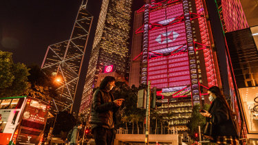 Pedestrians pass the illuminated HSBC headquarters  in Hong Kong. The bank is caught up in China and US tensions.