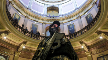 An armed protester wearing a mask stands at the Michigan Capitol Building in Lansing, Michigan.