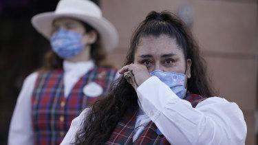 Karyawan Norali (nama belakang tidak diberikan), meneteskan air mata saat mereka bersiap untuk membuka gerbang Disneyland.