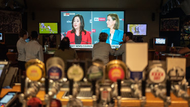 People watching the debate on TV between Queensland Premier Annastacia Palaszczuk and Opposition Leader Deb Frecklington at the Broncos Leagues Club.