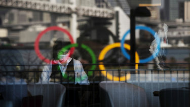 The Olympics rings are reflected on the window of a hotel restaurant as a server with a mask sets up a table in the Odaiba section of Tokyo.