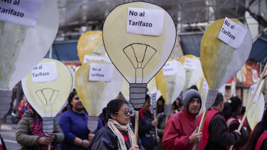 """People hold cutouts of light bulbs with words that read in Spanish """"no to the price hike"""" on Wednesday in Buenos Aires."""
