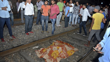 The body of a victim of a train accident lies covered in cloth on a railway track in Amritsar, India, on Friday.