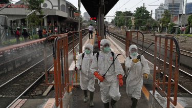 Members of the Indonesian Red Cross Society spray disinfectants on railings on a platform at the Kemayoran train station in Jakarta.