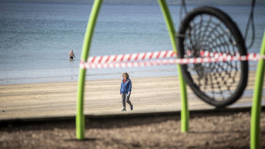 A woman walks past a closed off playground in Auckland.