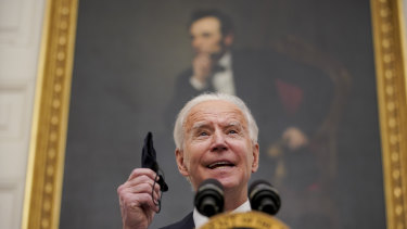 US President Joe Biden holds a protective mask while outlining his administration's Covid-19 response.