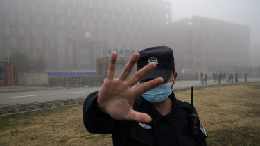 A security guard moves journalists away from the Wuhan Institute of Virology as the WHO team arrives for a field visit in February.