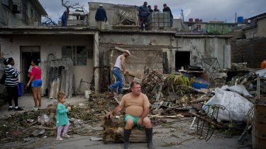 A man rests on the trunk of a tree as he rests from removing rubble from his home in Regla, Cuba.