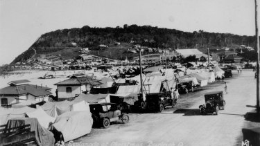 The Esplanade at Burleigh Heads crowded with tents and cars during Christmas holidays, 1932. Tents have been erected along the road and on the beach, turning the Esplanade into a camping site.