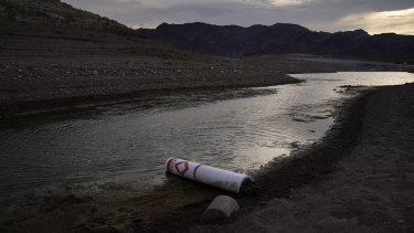 A buoy once used to warn of a submerged rock rests on the ground along the waterline near a closed boat ramp on Lake Mead at the Lake Mead National Recreation Area.