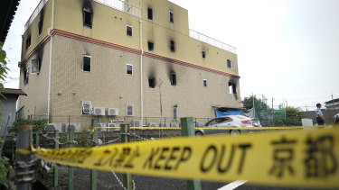 A police officer stands in front of the Kyoto Animation Studio building consumed in an arson attack on Thursday.