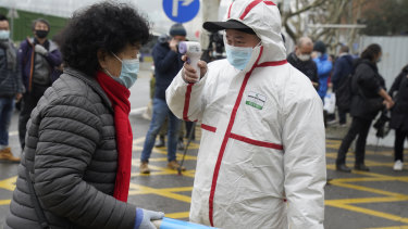 A worker in protective overalls takes the temperature of a woman entering the Hubei Centre for Disease Control and Prevention as the World Health Organisation team makes a visit.