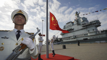 On the rise: a Chinese honour guard raises the Chinese flag during the commissioning ceremony of China's Shandong aircraft carrier at a naval port in Sanya.