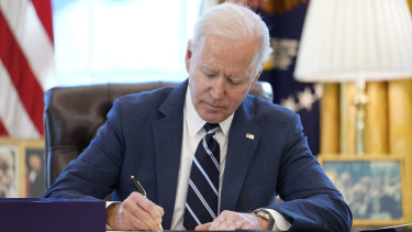 US President Joe Biden signs the American Rescue Plan, a coronavirus relief package, in the Oval Office of the White House.