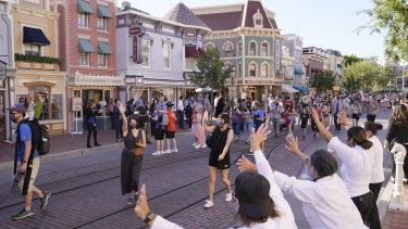 Para tamu disambut oleh staf, kanan, di Main Street USA di Disneyland.