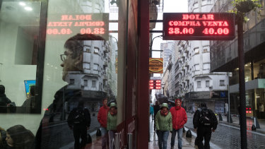 A sign displaying US dollar exchange rates hangs as people wait inside of a currency exchange house in Buenos Aires, Argentina. Argentina's currency crisis intensified last week as the peso plunged 20 per cent.