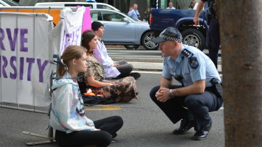 Extinction Rebellion protesters locked themselves to a barricade on the road in Brisbane's CBD on Wednesday morning.