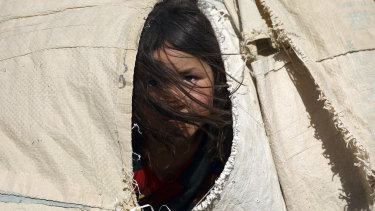 An internally displaced Afghan girl peers from her makeshift tent at a camp on the outskirts of Mazar-e-Sharif, Afghanistan.