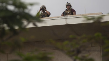 US soldiers stand guard on the rooftop of the US Embassy.