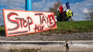 "A sign reading ""Stop the taxes"" sits by the highway behind demonstrators wearing yellow vests (Gilets jaunes) and holding a French national flag during a protest against fuel costs near Rodez, France, on Saturday."