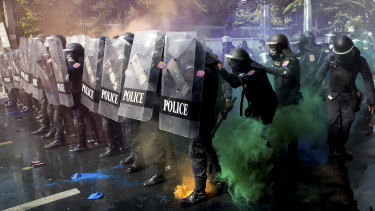 Riot police stand in formation as pro-democracy protesters throw smoke bombs.