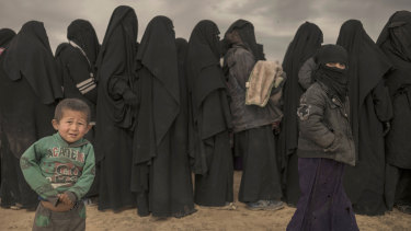 Women and children stand in line at a reception area for people evacuated from the last shred of territory held by Islamic State.