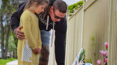 Sienna Stephens and her father Mark from Lancefield, leave flowers.