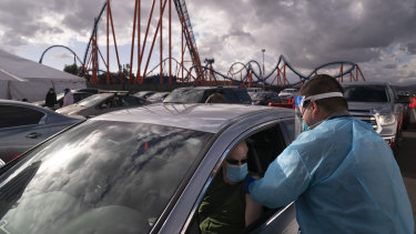 A nurse administers the COVID-19 vaccine at a mass vaccination site set up in the parking lot of Six Flags Magic Mountain in Valencia, California.