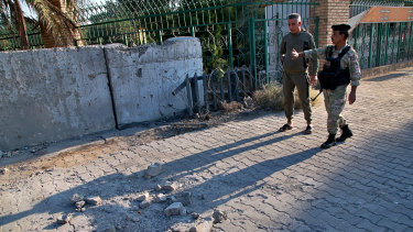Security forces inspect the scene of the rocket attack at the gate of al-Zawra public park in Baghdad, Iraq.