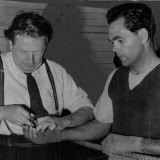 Trainer Tom Maguire adjusts Dave Sands' tapes before a workout at Newcastle prior to the Stadium bout with American Henry Brimm, August 3, 1950.