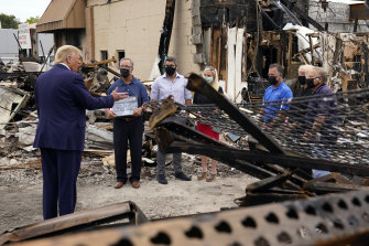 US President Donald Trump talks with owners of destroyed businesses as he tours an area damaged after a police officer shot Jacob Blake in Kenosha.