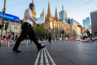Early morning commuters near Flinders Street station on the first day back after a snap five-day lockdown.