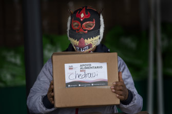 Pequeno Felino, a Lucha Libre wrestler, stands ready to hand out a food parcel.