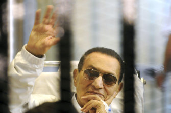 Hosni Mubarak waves to his supporters from behind bars as he attends a hearing in his retrial on appeal in Cairo in 2013.