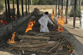 A family member performs the last rites of a COVID-19 victim at a crematorium in Jammu, India.