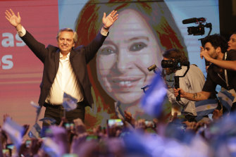 Peronist presidential candidate Alberto Fernandez waves to supporters in front of a large image of his running mate, former president Cristina Fernandez, after incumbent President Mauricio Macri conceded defeat.