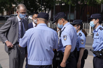 Australian ambassador to China Graham Fletcher, left, has his documents checked by policemen outside the No. 2 Intermediate People's Court. he was denied access to Yang Hengjun's case hearing.