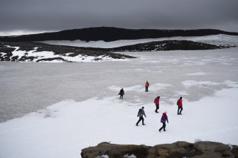 People walk on snow atop the Ok volcano crater on their way to the ceremony to mark the demise of the Okjokull glacier.