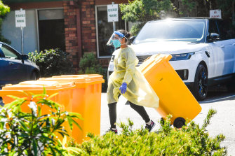 A staff member in protective gear disposes of waste at Estia Health in Keilor Downs on Monday.