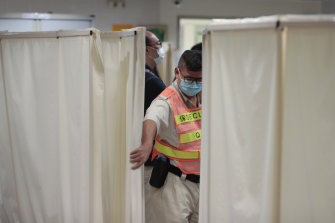 A security guard closes the curtain at the ICU ward where university student Alex Chow was being treated.