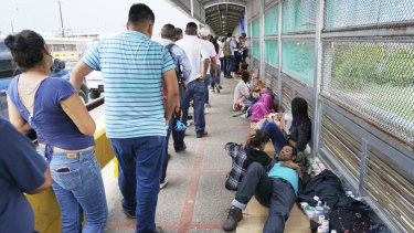 Migrant families rest from their travels to Matamoros, Mexico, along Gateway International Bridge which connects to Brownsville, Texas, as they seek asylum in the United States.