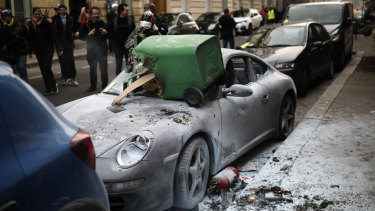 A trashed Porsche car is pictured during scuffles with riot police during the 13th weekend of protests throughout France on Saturday.