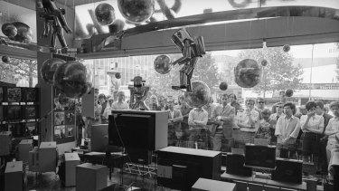 Mesmerised viewers watch the Apollo 11 moon landing.