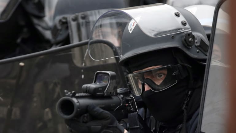 A police officer aims a flash ball gun during clashes with yellow vest protesters on the famed Champs Elysees avenue in Paris on Saturday.